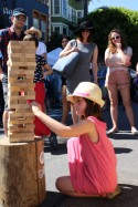 Sienna Haubert removes a piece of the over-sized Jenga puzzle with much concentration on the corner of Hayes and Octavia streets during the Urban Air Market on Sunday May 1, 2016. (BayNewsNow/Kaylee Fagan)